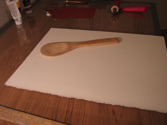 The block is flipped over with the paper on top, ready to be pressed with the wooden spoon